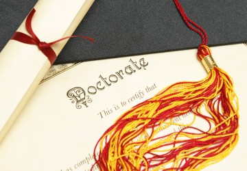 A closeup shot of a doctorate and diploma scroll with the tassels of a mortar board.