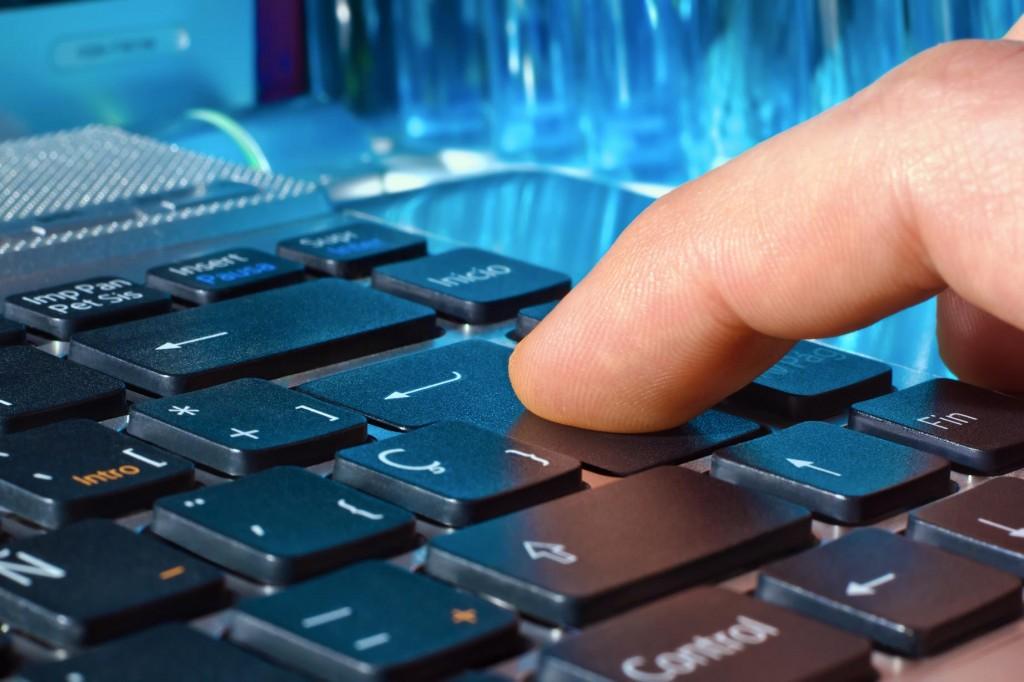 finger pressing the Enter key in laptop